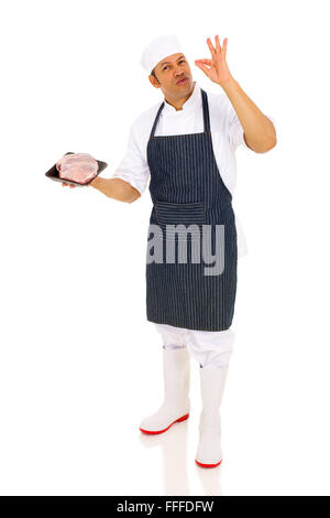 professional mid age male butcher holding raw meat and making delicious hand sign - Stock Photo
