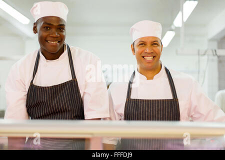 portrait of smiling multiracial butchery co-workers looking at the camera - Stock Photo