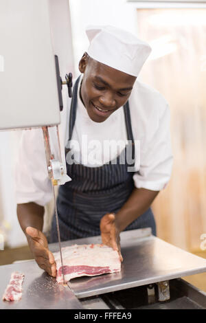 good looking African American butcher slicing meat on bandsaw - Stock Photo