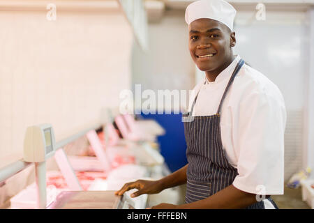 portrait of African butcher standing next to scale in butchery - Stock Photo