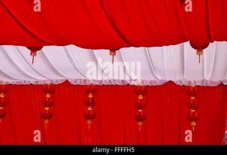 Red and white tent hanging with red lanterns decorating the reception area of a traditional Chinese wedding - Stock Photo