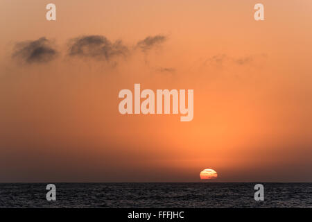 Rising sun partially hidden with clouds from behind the sea - Stock Photo
