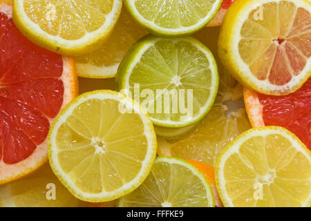 Citrus food background, Sliced Lemons and Limes and pink grapefruit - Stock Photo