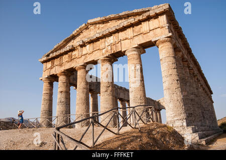 Ancient Greek temple with a tourist taking a picture in front of it. Segesta, Sicily, Italy. - Stock Photo