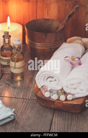 Spa treatment setting with frangipani, essential oil, scented candle  and towels for spa.  Macro selective focus - Stock Photo