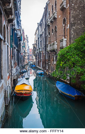 Venice, Italy - 13 February 2016: View of private boats moored up outside residential properties in a quiet canal - Stock Photo