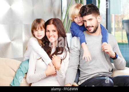 Portrait of happy young family with two kids sitting at sofa and smilig. Happy father giving piggyback to his cute - Stock Photo