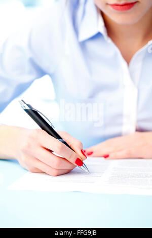 Close-up portrait of businesswoman filling the form on job interview. Business person sitting at desk while working - Stock Photo