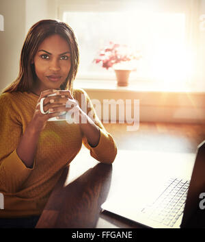 Beautiful Black woman in yellow sweater sitting at table holding coffee cup next to laptop with bright light coming - Stock Photo