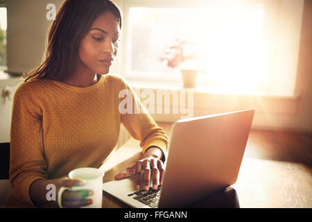 Serious Black adult single female sitting at table holding coffee cup and typing on laptop with light flare coming - Stock Photo
