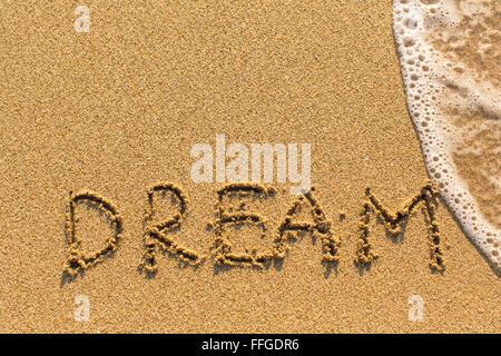 Inscription Dream on sea beach sand, with the wave. - Stock Photo