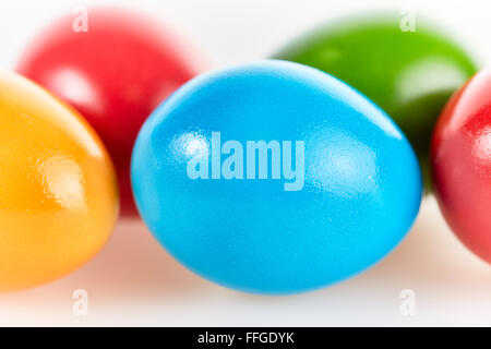 Five colorful easter eggs in different colors lying on white background - Stock Photo