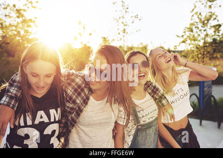 Group of teenagers hanging out, laughing in the summer - Stock Photo