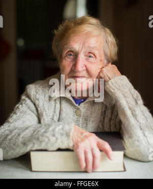 Portrait of elderly woman sitting with book. - Stock Photo