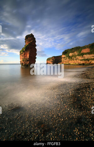 A sandstone sea stack at Ladram Bay near Sidmouth in South East Devon, bathed in early morning light in mid September. - Stock Photo