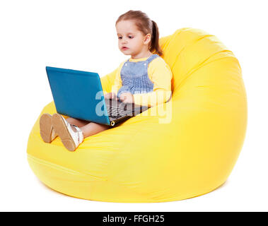 Child  sitting on a bean bag with laptop - Stock Image - Stock Photo