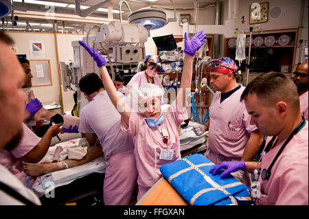 A TRU physician makes her way around the bed of an incoming patient while CSTARS students and TRU technicians rush - Stock Photo