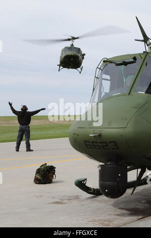 A mechanic from the 54th Helicopter Squadron guides a UH-1N Huey to the landing pad at Minot Air Force Base, N.D. - Stock Photo