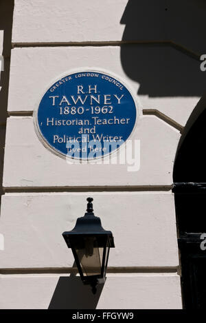A commemorative blue plaque for R.H Tawney (30 November 1880 – 16 January 1962) on display on a wall in London, - Stock Photo