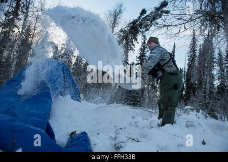 Capt. Bart Spendley, 274th Air Support Operation Squadron, air liaison officer, tosses snow to create an A-frame - Stock Photo