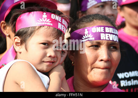 Philippines. 14th Feb, 2016. A young kid is carried by his mother during the One Billion Rising event in Rizal Park, - Stock Photo