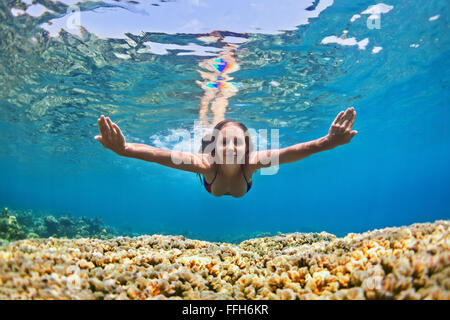 Happy beautiful girl - young woman dive underwater with fun over coral reef in sea pool. - Stock Photo