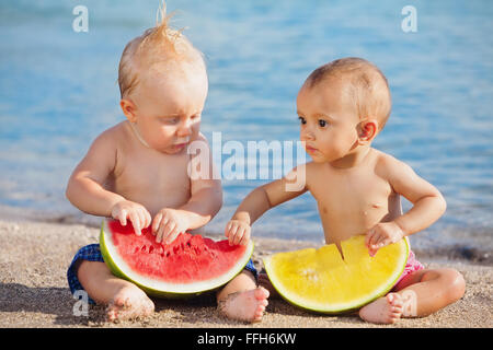 After sea swimming asian baby girl and white boy have a fun and eat fresh fruits on sand beach. - Stock Photo