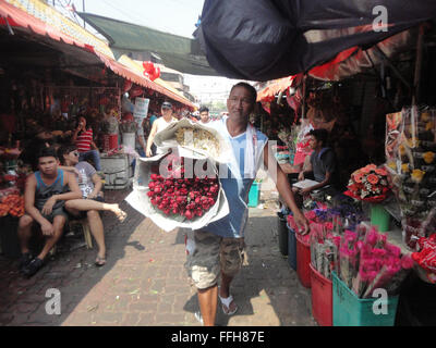 Manila, Philippines. 14th Feb, 2016. Filipinos carry bouquets of roses along the Dangwa flower market in Manila, - Stock Photo