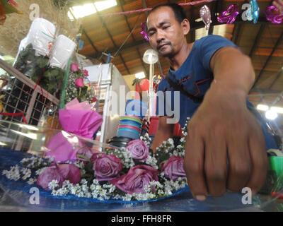 Manila, Philippines. 14th Feb, 2016. A Filipino florist arranges flowers at the Dangwa flower market in Manila, - Stock Photo