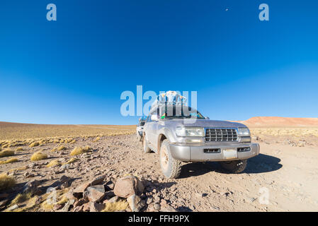 4x4 vehicle taking tourists on the desertic highlands of the Andes in Bolivia, roadtrip to the world famous Uyuni - Stock Photo
