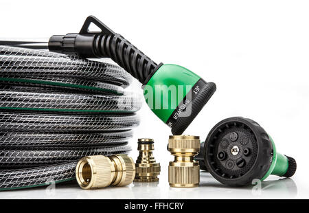A  garden hose with a sprayer and fittings on a white background - Stock Photo