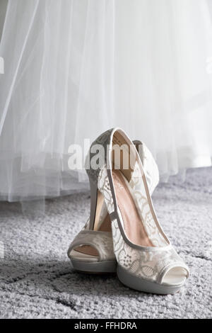 A brides shoes sit crossed, below her dress on carpet waiting to be worn during the wedding day - Stock Photo