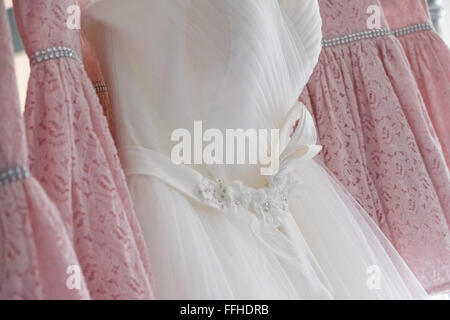 A traditional white wedding dress hung amongst four pink bridesmaids gowns - Stock Photo