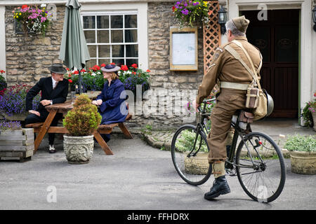 Participants in a Britain at war re-enactment day in WW2 period 1940's dress, outside a pub in the United Kingdom - Stock Photo