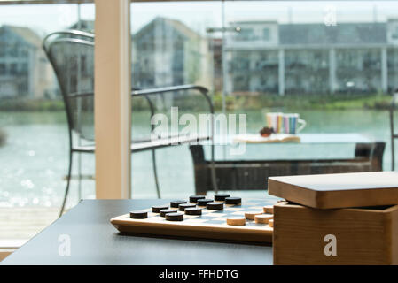 A checkers board, set, awaiting opponents to start a game in a holiday home overlooking water - Stock Photo