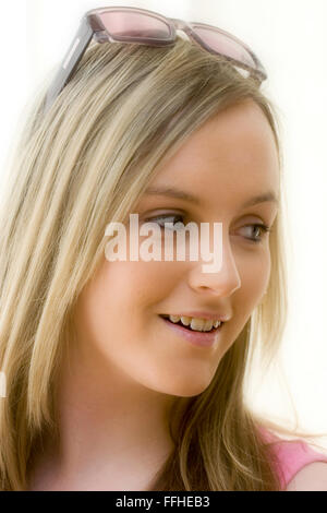 Caucasian blonde blue eyed teenage girl, wearing Christian Dior sunglasses on top of head. half turned away, smiling. - Stock Photo