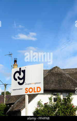 An estate agents sign outside a thatched cottage in Uffington, Oxfordshire, England, UK. - Stock Photo