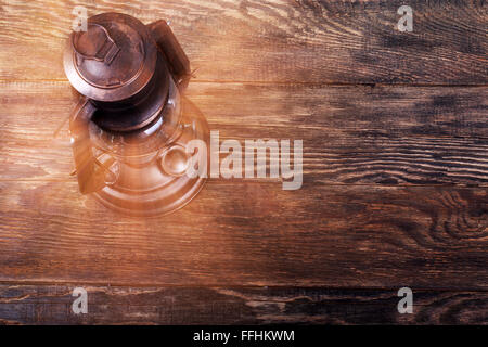 Old rusty kerosene lantern on wooden structured floor - Stock Photo