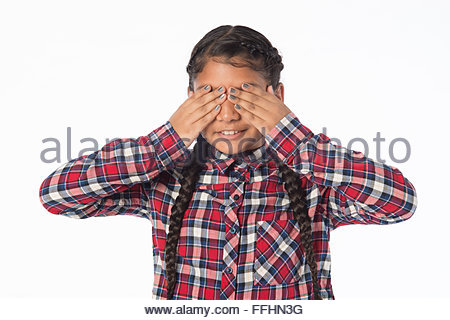 young Asian Indian girl standing on a white background in casual school cloths with her hands covering her eyes - Stock Photo