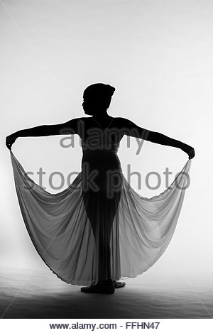 young girl ballerina dancing with her arms outstretched silhouetted against a white background. - Stock Photo
