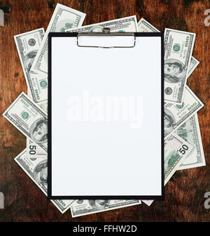 Blank paper sheet in clipboard placed on center of money dollar and old wood background. Business plan and other - Stock Photo