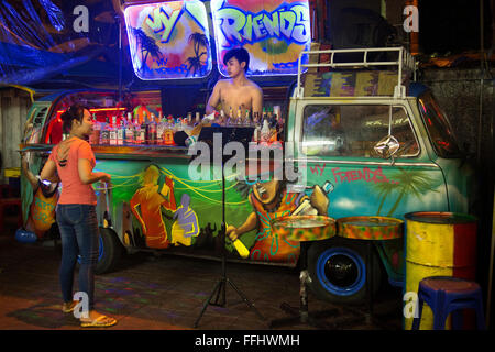 A VW Volkswagen bus cocktail bar in Soi Rambuttri. Bangkok. Grab a beer with ice or a cocktail from one of the pop - Stock Photo
