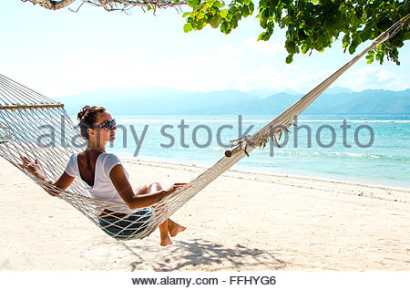 Girl relaxing in hammock on the beach near blue ocean. Bali, Indonesia. Stock image. - Stock Photo