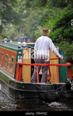 Man navigating a narrow boat on the Llangollen Canal in Wales, UK. - Stock Photo