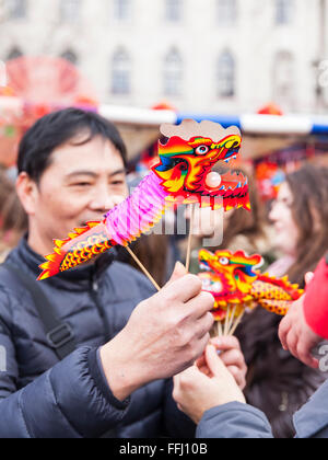 London, UK. 14th Feb 2016. A man holds colourful Chinese dragon figurines. Thousands of people enjoy the Chinese - Stock Photo