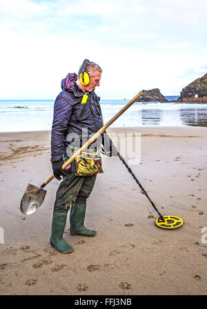 Man using a metal detector on portreath beach in cornwall, uk - Stock Photo