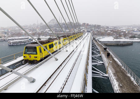 Istanbul subway metro train passing and people walking on the Golden Horn Metro Bridge on a snowy day near Halic - Stock Photo