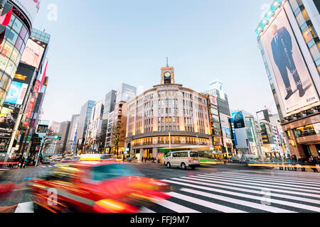 Tokyo, Japan - January 18, 2015:  Ginza shopping district at rush hour in Tokyo, with the iconic Ginza Wako building - Stock Photo