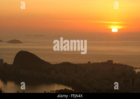 Rio de Janeiro, Brazil, 14th February. The sun rises in the sea, with Ipanema in the foreground, seen from Vista - Stock Photo