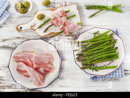 Fresh asparagus wrapped in bacon on a wooden table. Top view - Stock Photo